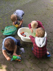 Kinder beim Spielen mit den Paw Patrol Figuren im Wasser